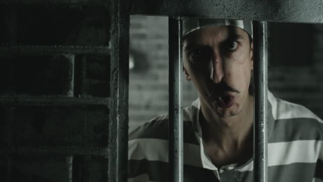 angry men looking at camera from prison cell - claustrophobia stock videos and b-roll footage