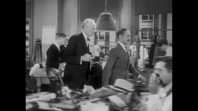1931 Angry newspaper editor (Adolph Menjou) strides across newsroom insisting on specific reporter for job