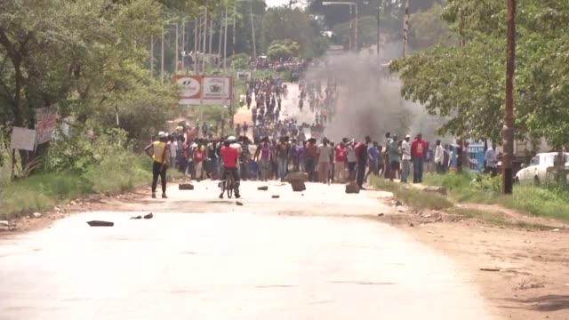 angry protesters barricade roads with burning tyres and rocks in zimbabwe after the government more than doubled the price of fuel in a bid to... - repubblica dello zimbabwe video stock e b–roll
