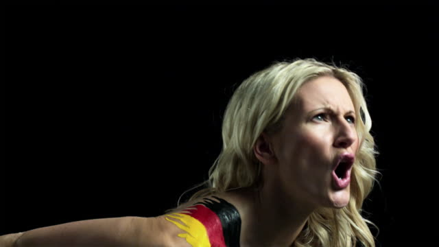 Angry woman shouting with German flag painted on shoulder