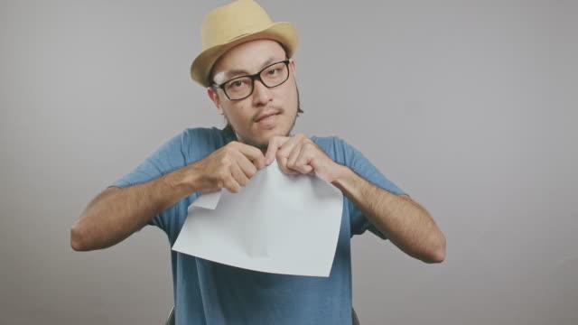 vidéos et rushes de jeune hipster fâché déchirant le papier et criant isolé dans le fond gris. homme asiatique avec le chapeau et les glaces devant l'appareil-photo. tir moyen. - objet en papier