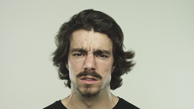 angry young man against gray background - displeased stock videos and b-roll footage