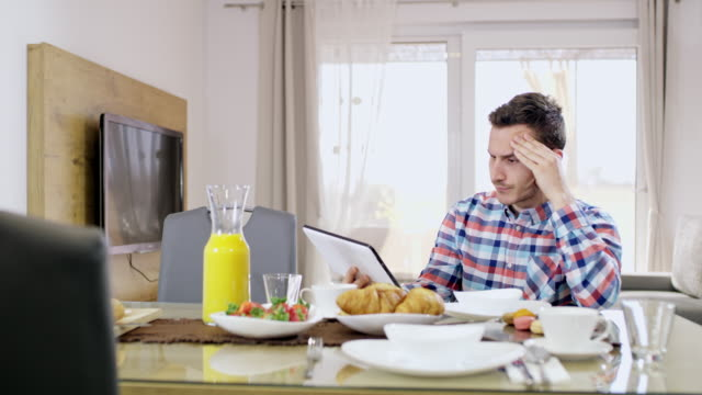 ds ws angry young man using a tablet while having breakfast - rabbia emozione negativa video stock e b–roll