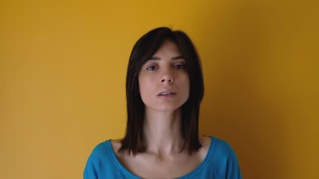 vidéos et rushes de femme jeune en colère sur fond jaune - série d'émotions
