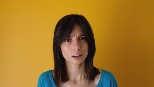 angry young woman on yellow background - displeased stock videos & royalty-free footage