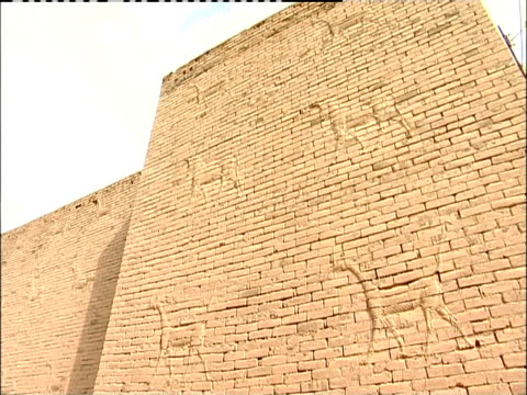 animal figures cover a brick wall inside the ancient city of babylon. - babylon stock videos and b-roll footage