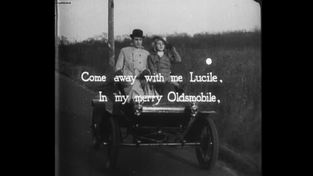 1931 animated moon bounces along song lyrics as man and woman drive oldsmobile down the road - 平手打ち点の映像素材/bロール