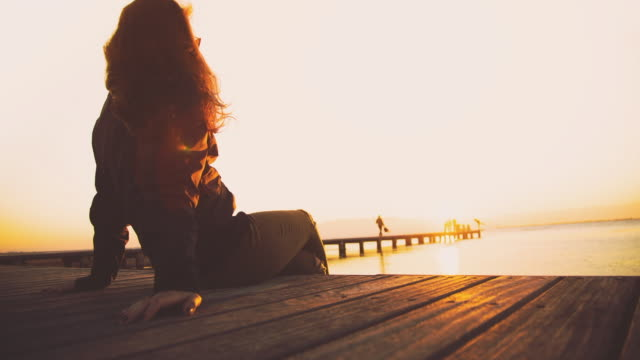 Animated picture of a Beautiful girl sitting and contemplating the sunset over the Ebro Delta in the Mediterranean sea from wood pier and stunning sunlight during a weekend travel in the region with hair flying with the wind.