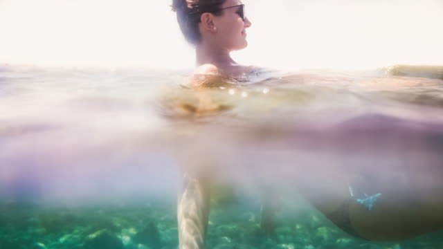 Animated picture of a beautiful traveler girl enjoying the Tenerife natural pool waters swimming with stunning light during travel vacations in Canary Islands with warm and sunny days.