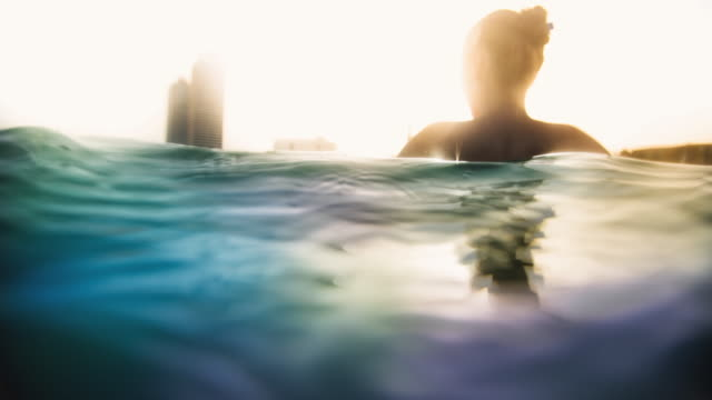 Animated picture of a girl enjoying beach swimming in the Barcelona city with cityscape at sunset floating on water, footage with cinemagraph effect of the water in motion.
