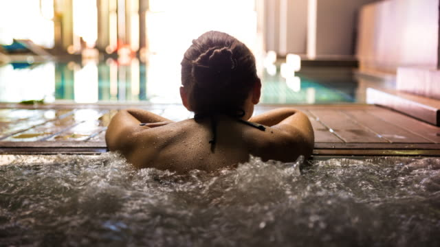 vídeos de stock e filmes b-roll de animated picture of a woman relaxing in a hot tub pool during weekend days of relax and spa in a luxury place during travel vacations. - spa