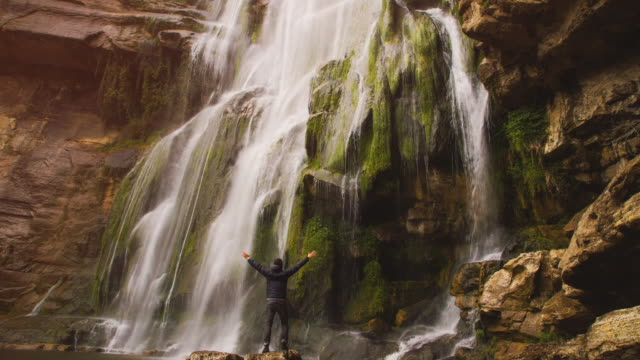 Animated picture with cinemagraph effect of a excited guy with arms raised under a huge waterfall with water in slow motion during the rainy season in Catalonia during weekend adventure trip.