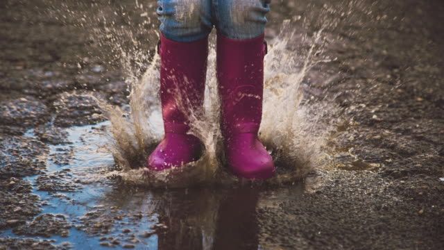Animated picture with cinemagraph effect of a girl jumping over water puddle during rainy day in the city asphalt with nice splashing drops and purple boots.