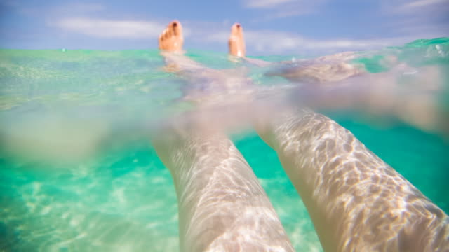 vídeos de stock e filmes b-roll de animated picture with cinemagraph effect of a traveler girl swimming and enjoying alone the beautiful beach during travel vacations in the fuerteventura island with nice water colors and water in motion. - 25 29 anos