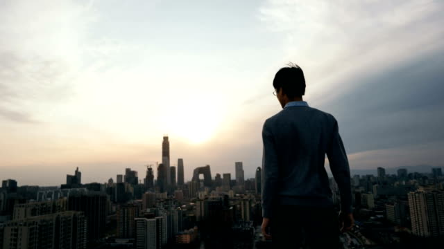 animated picture with cinemagraph effect of man looking far away in thought in city - 後ろ姿点の映像素材/bロール