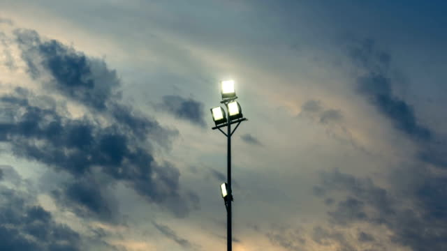 animated picture with cinemagraph effect of stadium lights glowing in front of darkening sky - floodlight stock videos & royalty-free footage