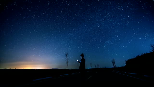 vídeos de stock e filmes b-roll de animated picture with cinemagraph effect of woman using smartphone at starry night - astronomia