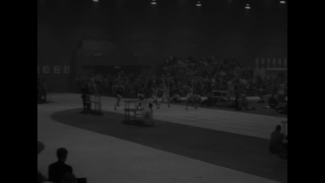 sports / title superimposed on indoor track danish miler star of dc track meet / chuck holding at high jump he grins for camera / vs men speed though... - star jump stock videos & royalty-free footage