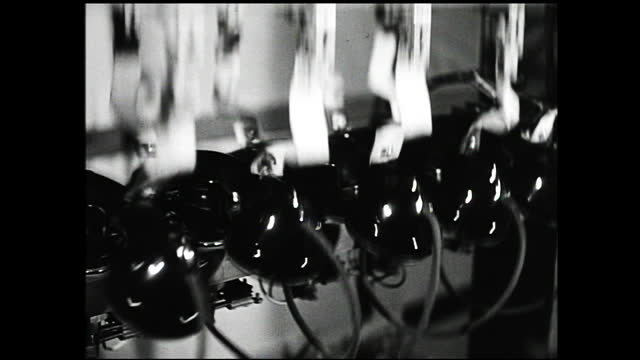 stockvideo's en b-roll-footage met animation of telephone cables connecting two buildings; row of women operators sitting in front of machines and a woman holding a telephone walks by;... - 1940 1949