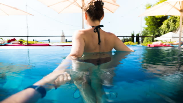 vídeos de stock, filmes e b-roll de animation picture of a happy woman swimming in outdoor overflowing swimming pool during romantic weekend days of relax and spa in a luxury place with boyfriend holding hands from boyfriend personal perspective. follow me. - lago infinito