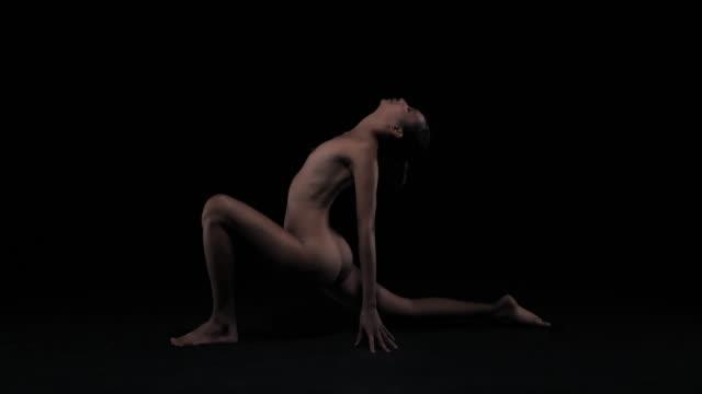 anjaneyasana (variation) pose :silhouette von eleganten jungen frau macht yoga-stretching-übungen, sie ist künstlerische akt zeigt ihren perfekten körper in dunklen studio. - fkk stock-videos und b-roll-filmmaterial