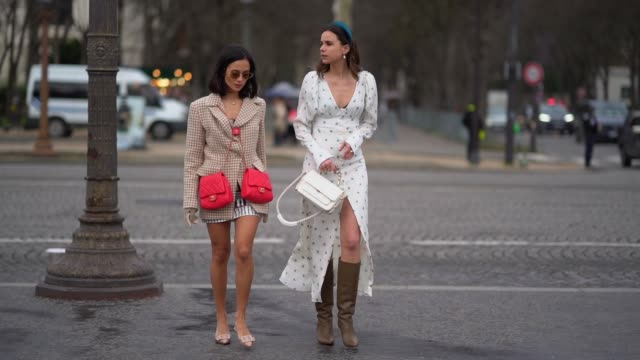 Anna Rosa Vitiello wears a blazer jacket double red Chanel bags a guest wears a headband a white dress with printed blue flowers a white Chanel bag...