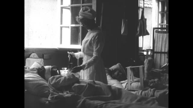WS Anne Harriman Vanderbilt wears nurse's uniform as she stands at bedside of wounded soldier pours him a drink and speaks to him as he drinks it /...