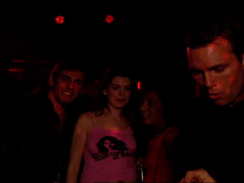 Anne Hathaway standing with guy and young woman on dance floor in club she acknowledges camera ZI as friend steps in front of Anne obstructing view