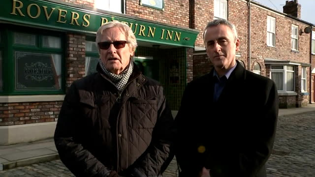 william roache leads tributes roache and roberts live 2way interview from coronation street set in manchester sot - ウィリアム・ローチ点の映像素材/bロール