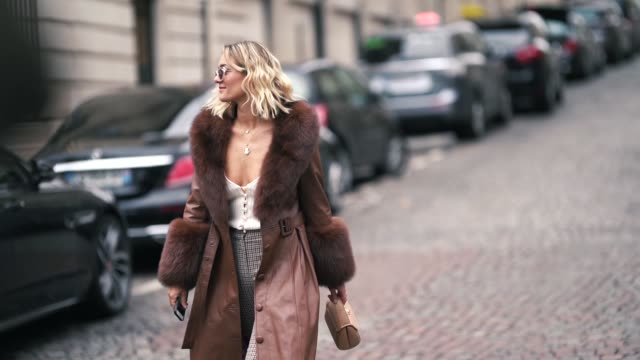 vidéos et rushes de anne laure mais wears sunglasses, a beige low-cut top, a brown leather coat with a fur collar and fur cuffs, light brown checkered pants, openwork... - beige
