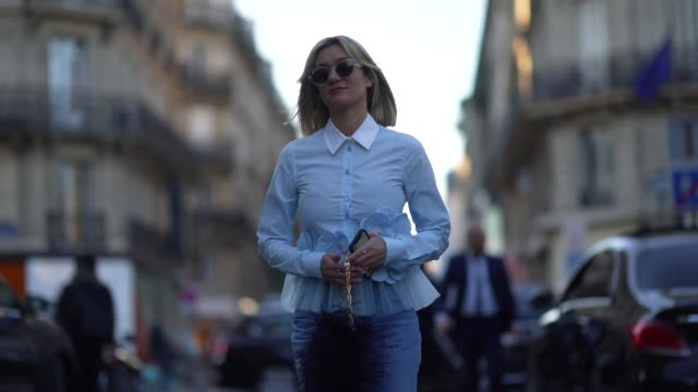 anne-laure mais wears sunglasses, a light blue ruffled shirt with a white collar and flowers embroidered, blue ripped jeans, light blue pointy pumps,... - paris fashion week - haute couture spring/summer 2020点の映像素材/bロール