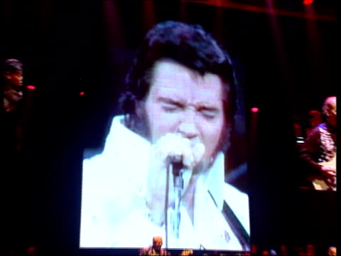 Anniversary of death LIB ENGLAND Hampshire Bournemouth INT Film recording of Elvis Presley singing on giant screen at concert venue PULL OUT to band...