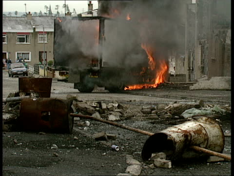 03 londonderry bogside 1252 vs burnt out single decker bus straddles road troops stand by bottles hit ground near troops and media van burning in... - 北アイルランド点の映像素材/bロール
