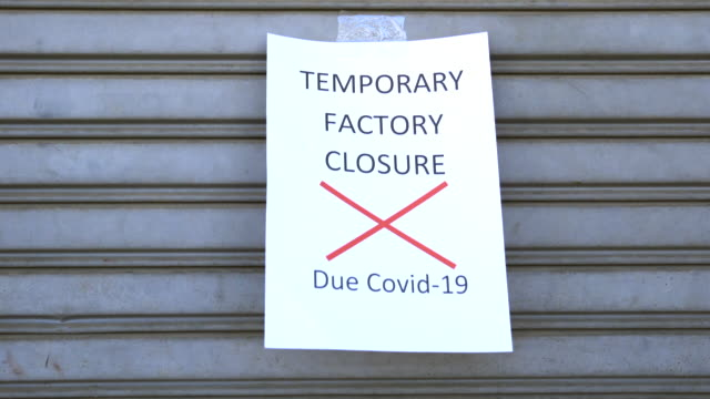 announcement paper that the factory could not continue to operate due to the virus outbreak was attached to the steel door in front of the factory. - plant stock videos & royalty-free footage