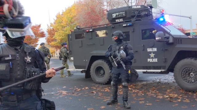 announcements are made to disperse by police as they patrol the area oregon state police and salem police guard the oregon state capitol building... - oregon state capitol stock videos & royalty-free footage