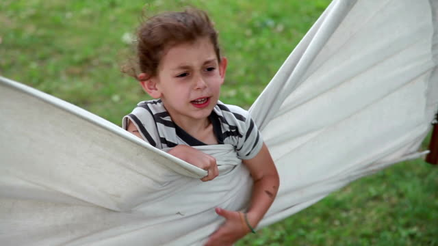 annoyed child hiding behind the hammock in the backyard - tragedy mask stock videos & royalty-free footage