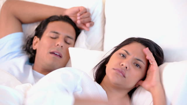 annoyed woman lying next to her snoring boyfriend - snoring stock videos and b-roll footage