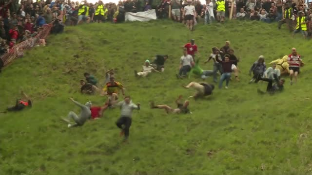 annual gloucestershire cheese rolling competition; england: gloucestershire: cooper's hill: ext various shots of competitors running and tumbling... - moving down video stock e b–roll