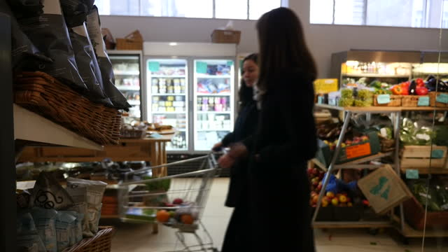 stockvideo's en b-roll-footage met anon interior shots of earth natural foods health food shop pack of dandelion coffee various people browsing products in shop plate of cupcakes on... - kentish town