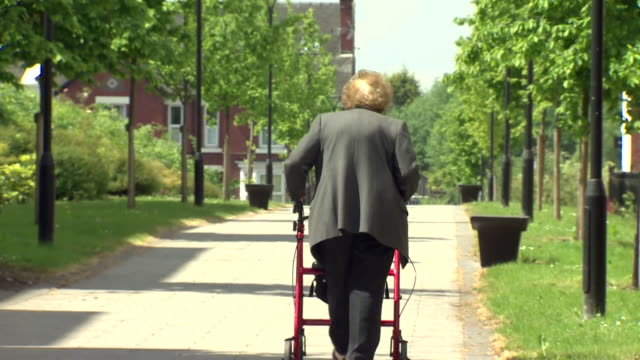 Anonymous elderly lady walking up path with aid of walking frame at retirement village Stafford
