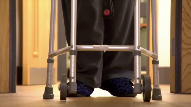 vídeos y material grabado en eventos de stock de anonymous elderly person walking down corridor using zimmer frame - servicios sociales