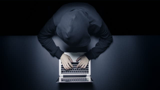 Anonymous hacker in the dark with laptop