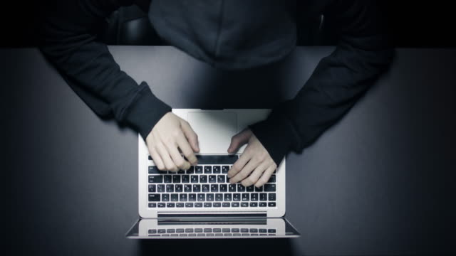anonymer hacker in der dunkelheit mit laptop - seeräuber stock-videos und b-roll-filmmaterial