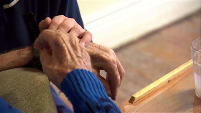anonymous hand of elderly lady touching the hand of her care worker in an old people's home - råmaterial bildbanksvideor och videomaterial från bakom kulisserna