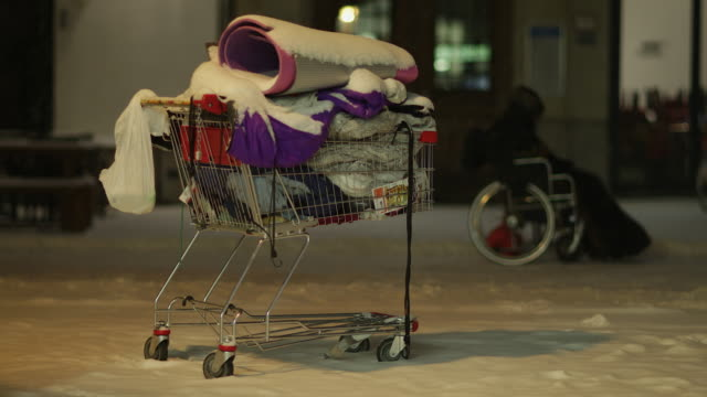 vídeos y material grabado en eventos de stock de anonymous homeless with wheelchair in winter night with snowfall in the city - sin techo