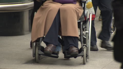 anonymous lady pushed along oxford street in wheelchair - oigenkänliga personer bildbanksvideor och videomaterial från bakom kulisserna