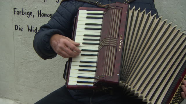 Anonymous man busking playing accordian in Berlin