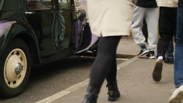 anonymous people pass vintage car - street style点の映像素材/bロール