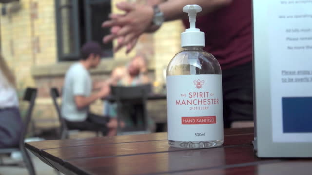 anonymous person putting on hand sanitizer at bar in trafford, during coronavirus pandemic - hygiene stock videos & royalty-free footage