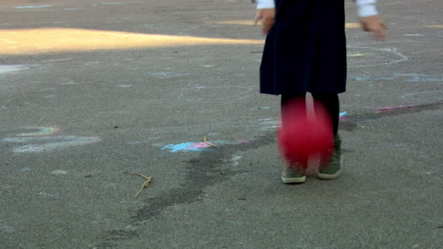 Anonymous school child bouncing red ball in playground